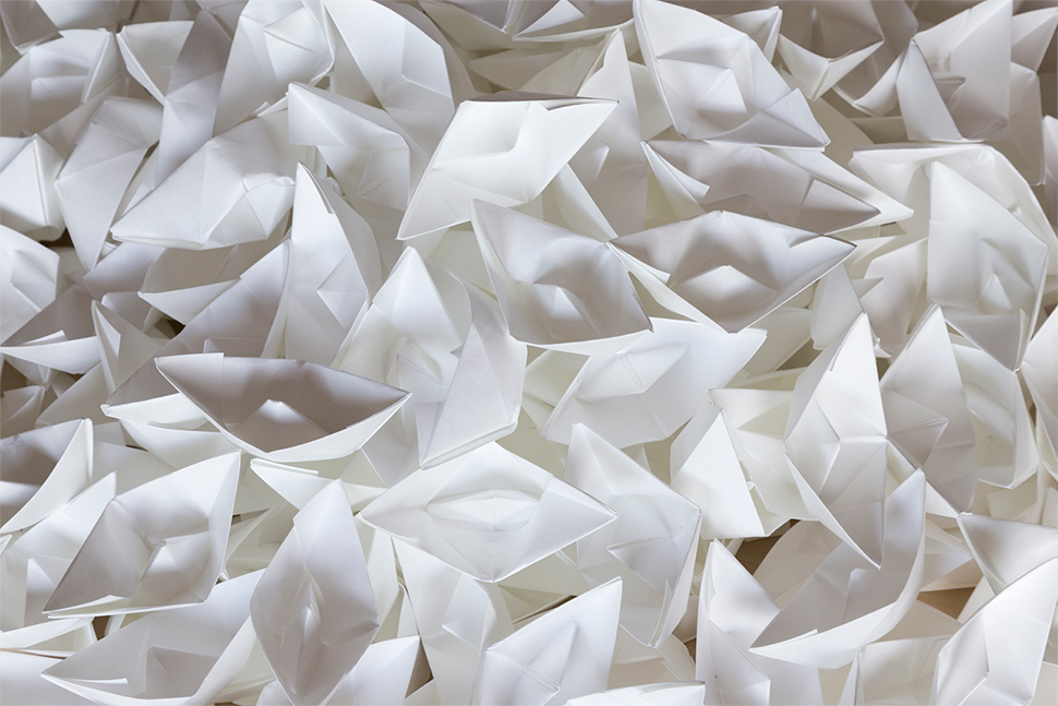 A photo looking down upon a pile of paper mache boats sitting atop of one another.