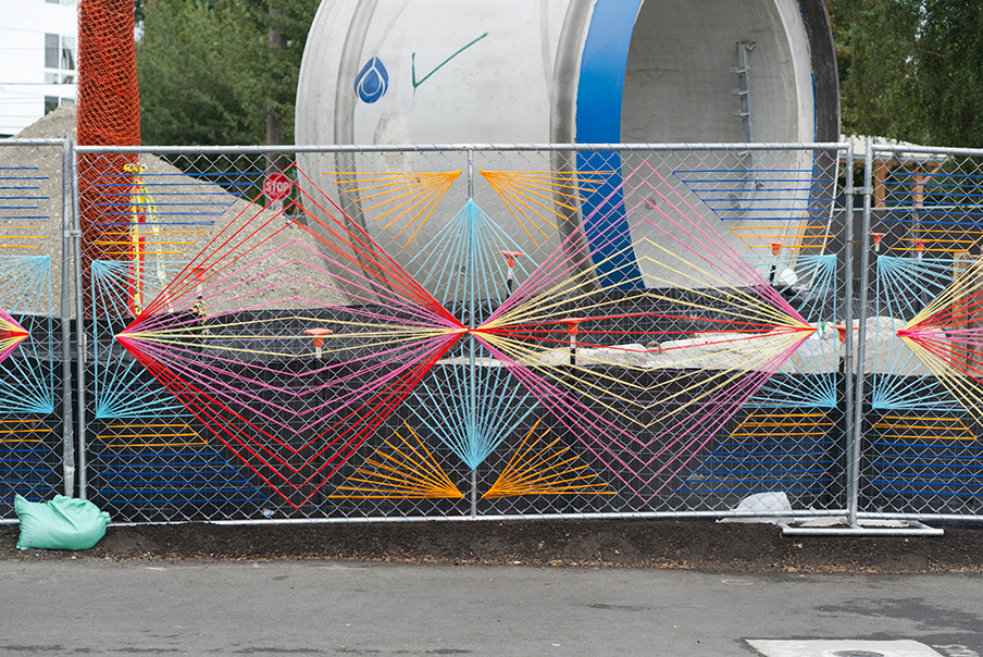 Christy Caravaglio's artwork made up of bright colored strands woven into a chain link fence in a geometric pattern, a large section of a pipe sits on the other side of the fence.