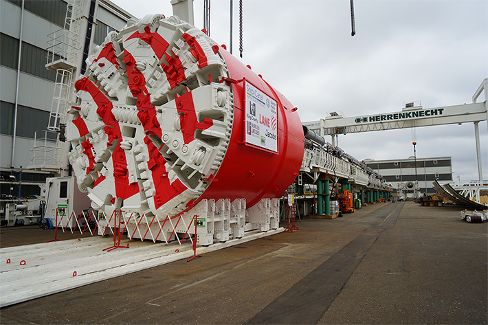 A large red and white tunnel boring machine at a construction site.