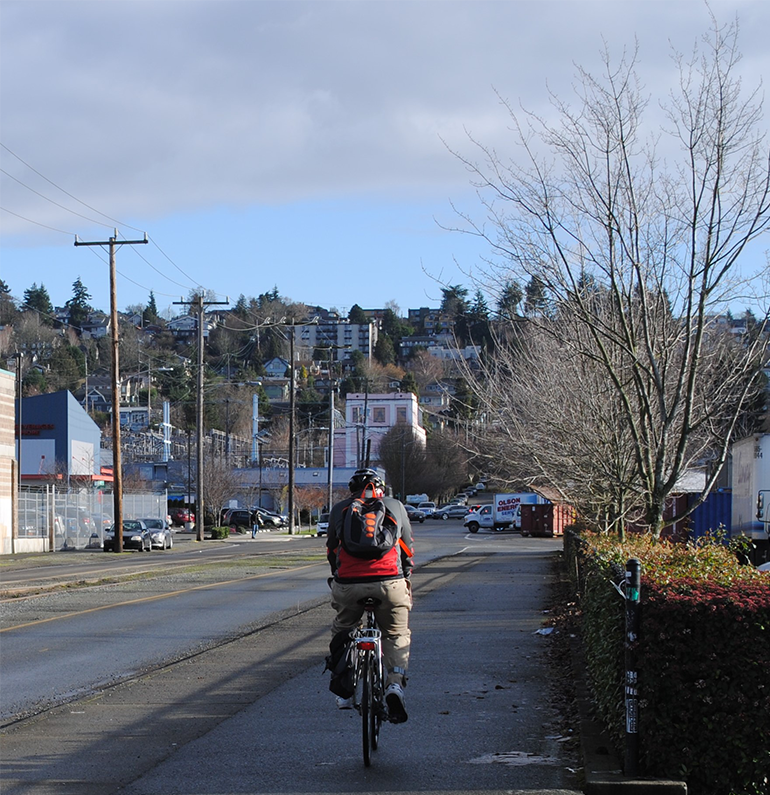 a cyclist with a backpack and helmet on rides East on NW 45th St towards 9th ave NW