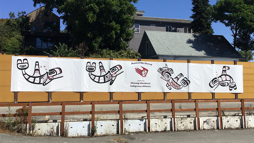 Murals placed along the Wallingford screen wall in late July 2020. The murals depict 4 killer whales and are drawn in form design. In the middle of the images is a white sign that states Protect the sacred, Missing Murdered Indigenous Women.