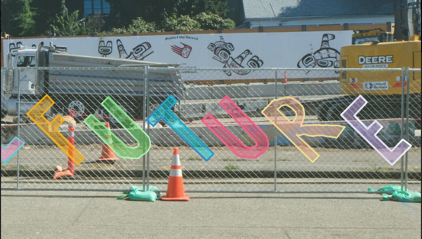 A chain link fence at a construction site. The word FUTURE has been graphically added to the front of the fence in large, colorful block lettering