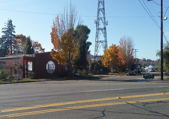 A red brick building beside a tree with orange leaves in the future site of Fremont vertical shaft at Leary Way Northwest and Northwest 36th Street.