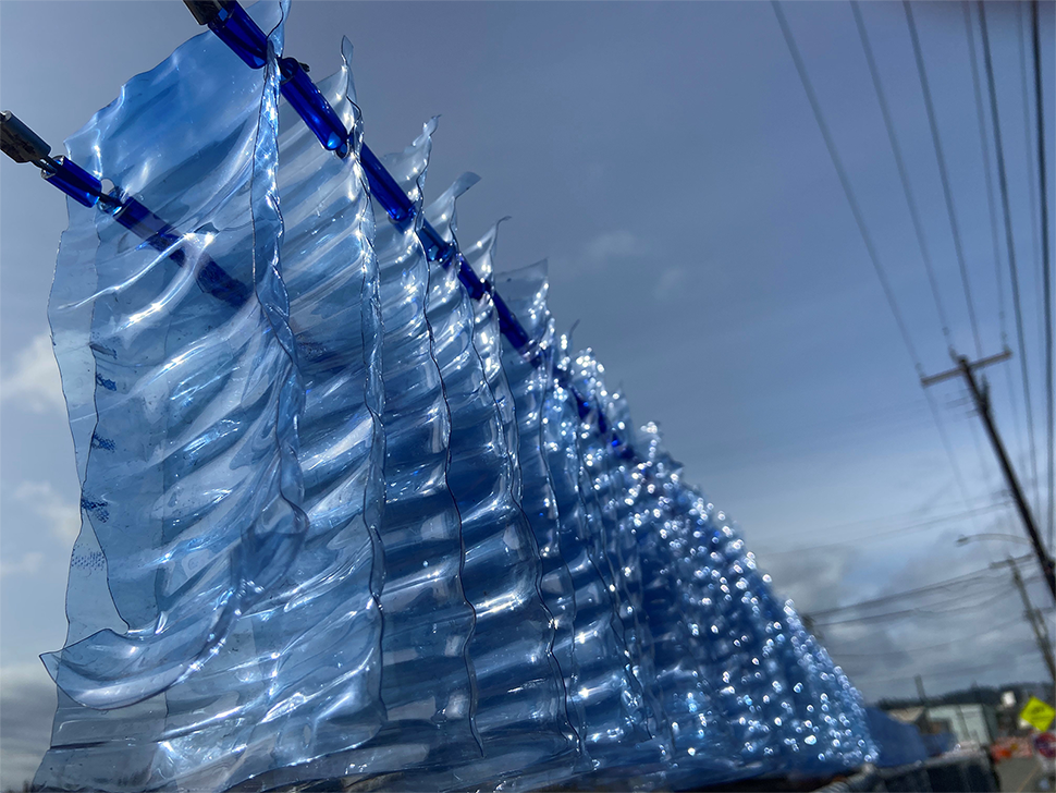 Blue plastic resembling ripples of water placed on top of a chain linked fence.