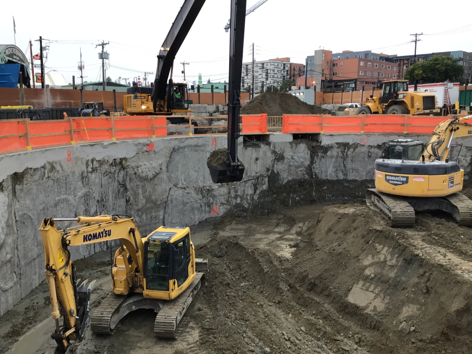 Three yellow excavators remove dirt from the vertical shaft site in Ballard