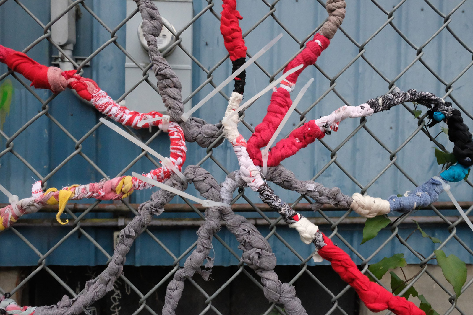 Colored t-shirts are tied to together and wrapped around a chain link fence to resemble a flower.