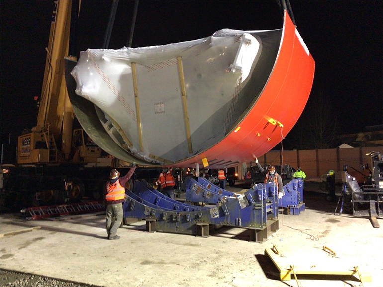 A large piece of the orange outer shield of the tunnel boring machine being lowered by a crane onto a cradle. Several people are helping to direct it.