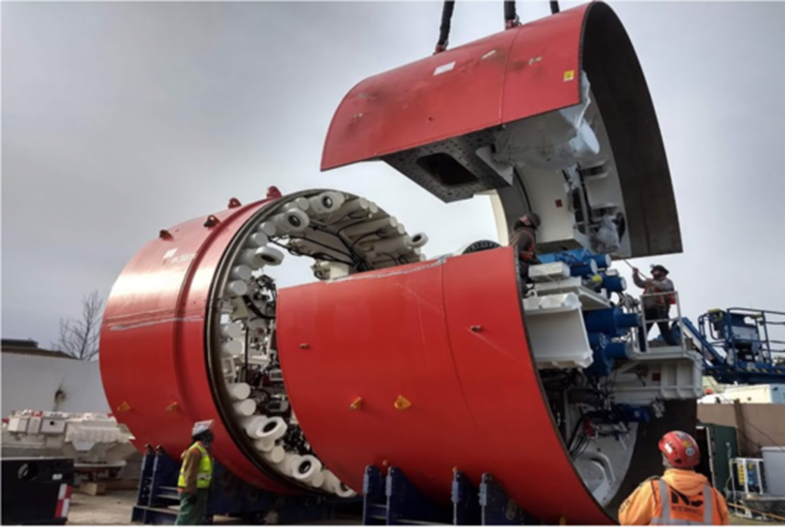 A large red tunnel boring machine is assembled by crane.
