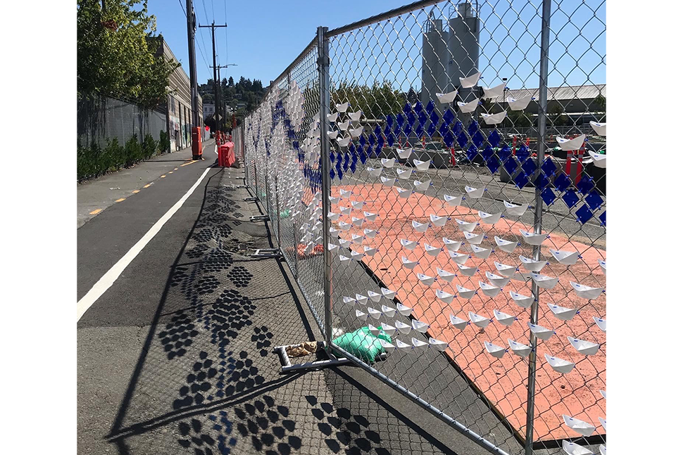 """White and blue paper-mache art work that resembles water flow with a blue sign that reads """"flow"""" along a chain link fence at dusk on a sunny day."""