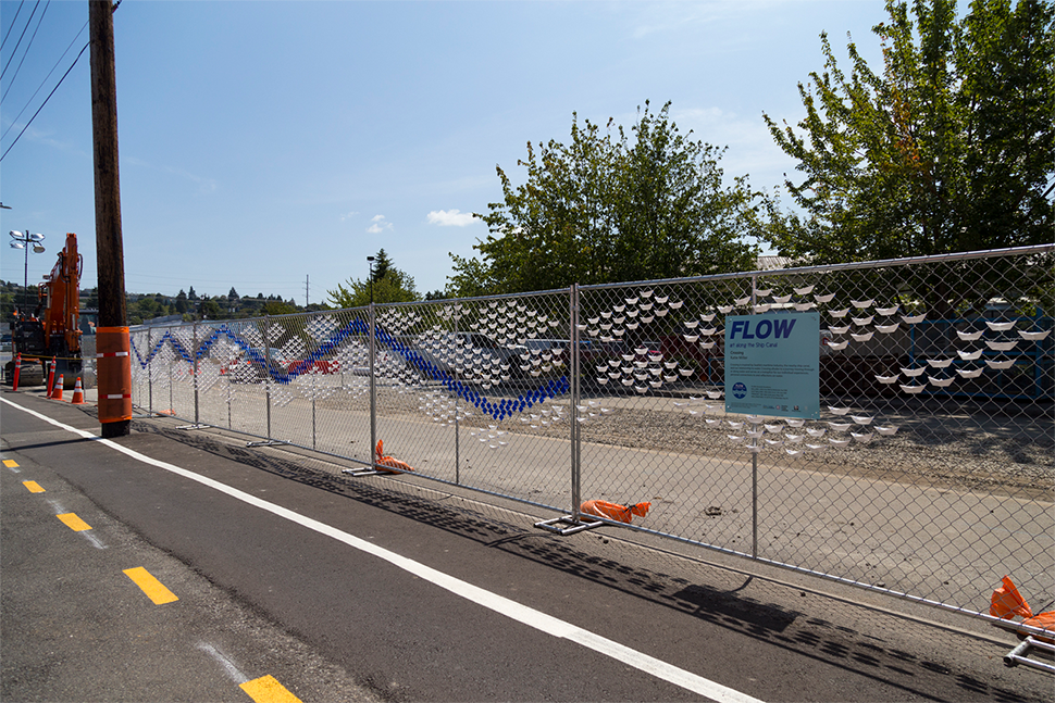 "White and blue paper-mache artwork that resembles water flow with a blue sign that reads ""flow"" along a chain link fence at dusk on a sunny day."