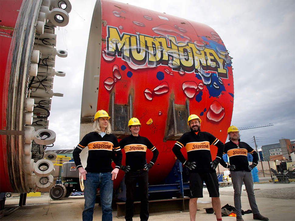 Four individuals wearing sweaters and hardhats stand in front of a tunnel boring machine that has the word MudHoney drawn in yellow and black letters