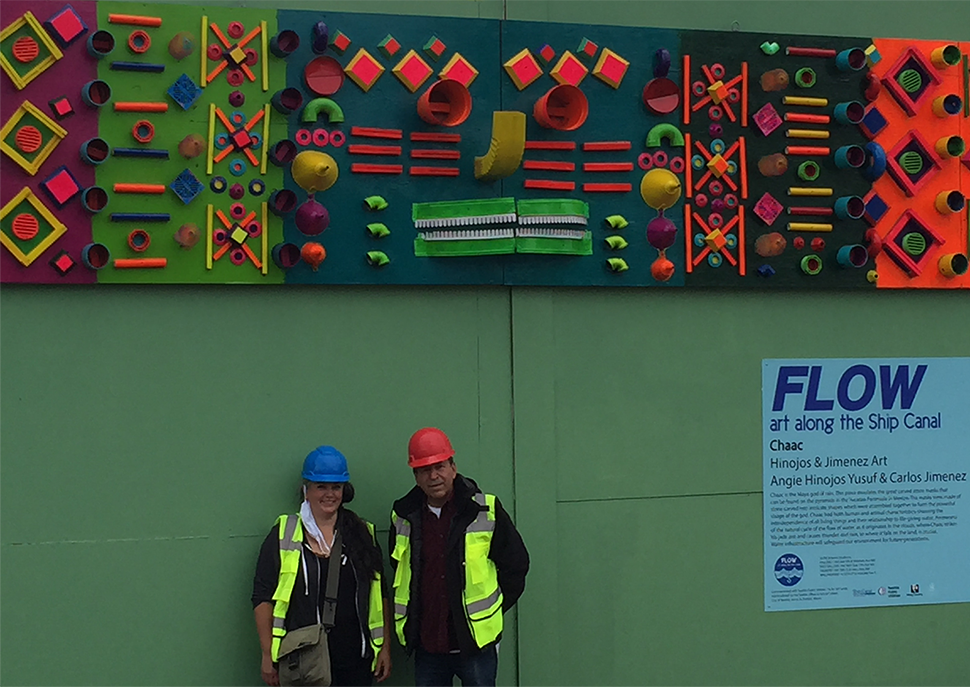 Two artists in yellow reflective jackets and hard hats stand in front of their artwork which consists of bright colored geometric shapes that illustrate the natural water cycle.