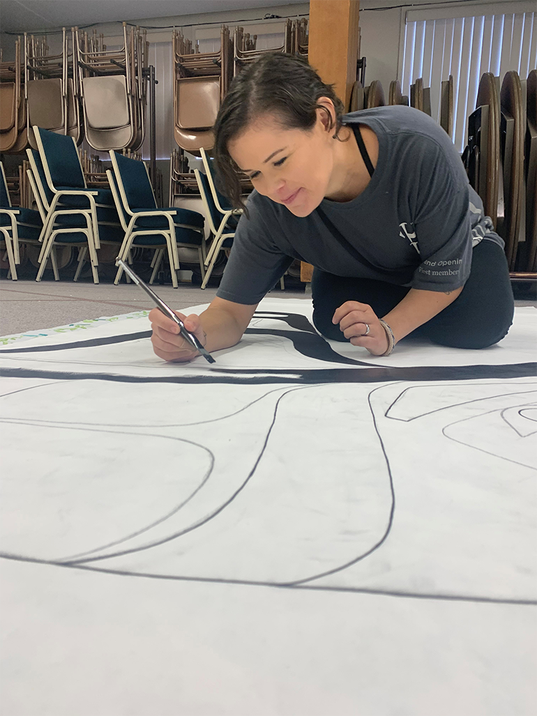 An artist colors in a mural with black paint on a large white piece of paper.