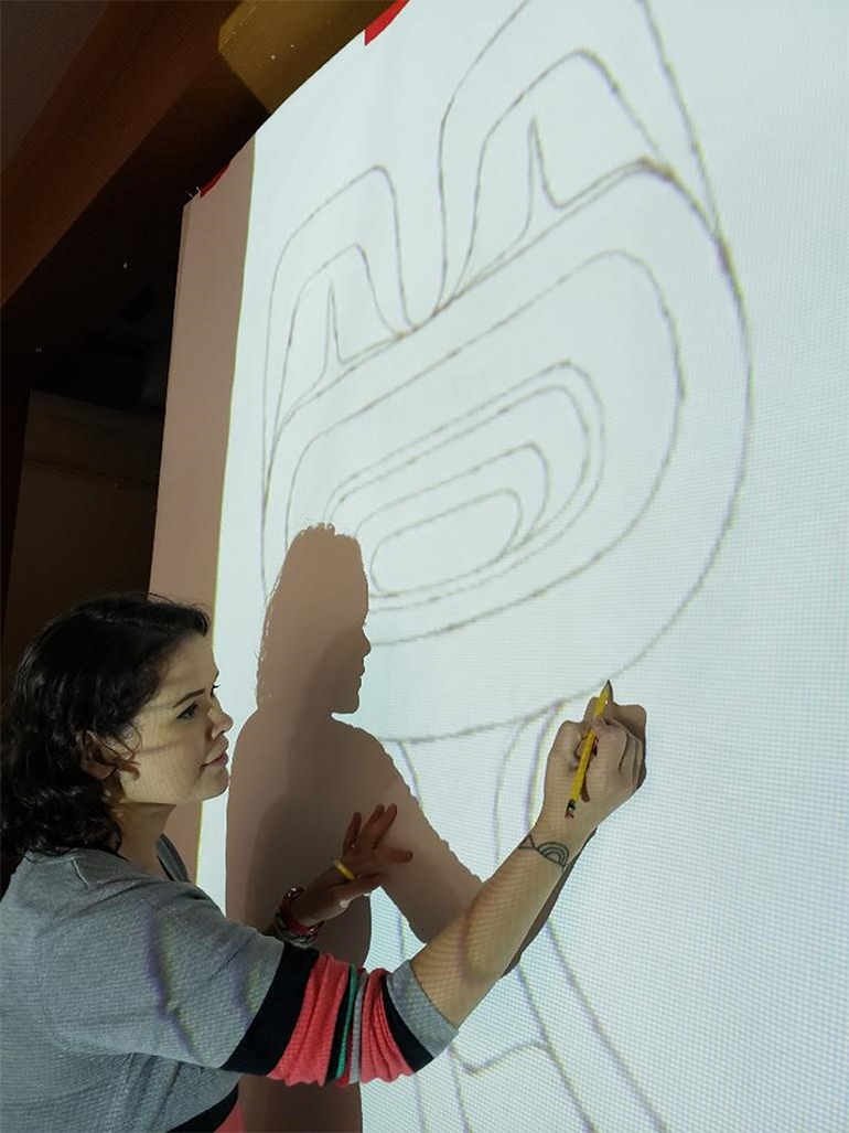 An artist draws a mural on a large white piece of paper against a wall using paper.