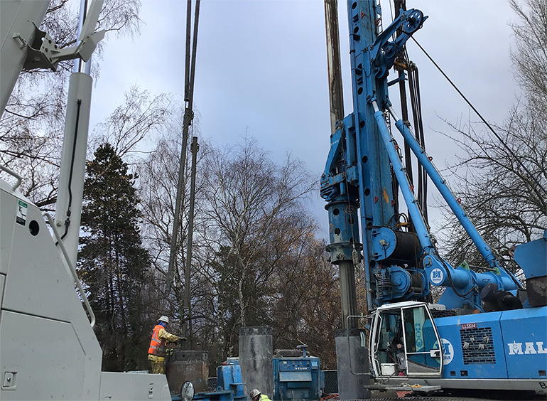 A large, blue double head drill is used to complete secant pile wall construction in Queen Anne.