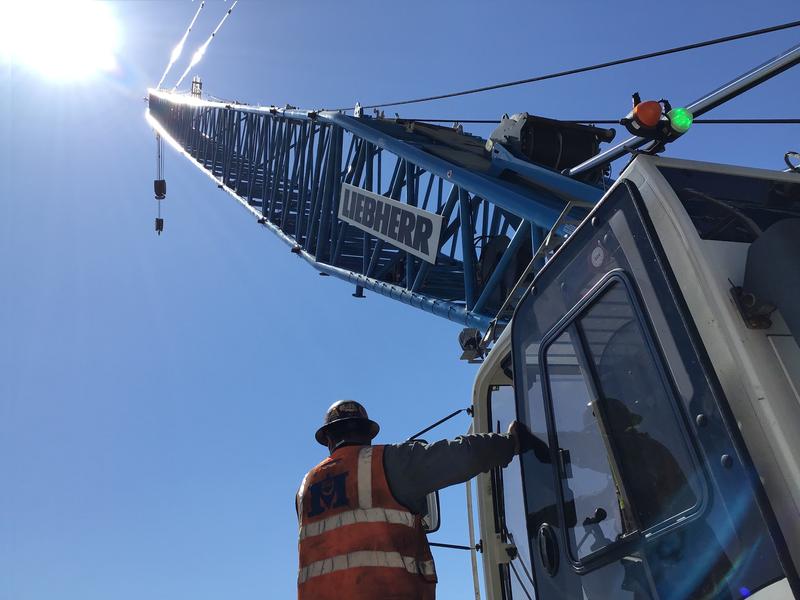 crane operator looks up at a crane
